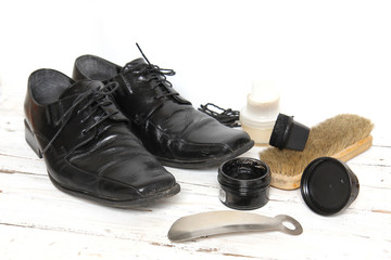 shoe care equipment and formal black shoe on white background