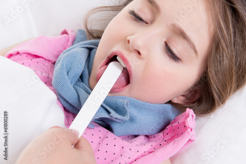 Pediatrician examining little girl's throat.