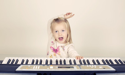 adorable funny little girl playing in synthesizer