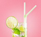 Glass of mojito cocktail on pastel pink background