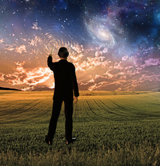 Man in suit touches sky creating ripples