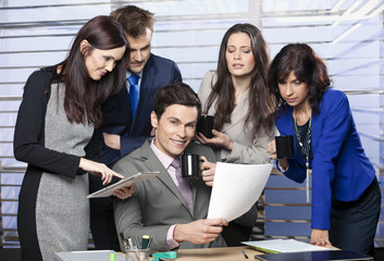 Group of friendly businesspeople with happy leader in office