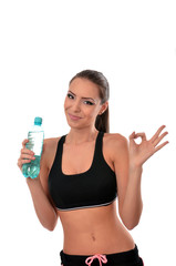 Fitness lady holding a bottle of water and giving the ok sign
