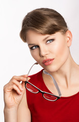 Beautiful blond model holding eyeglasses and looking aside