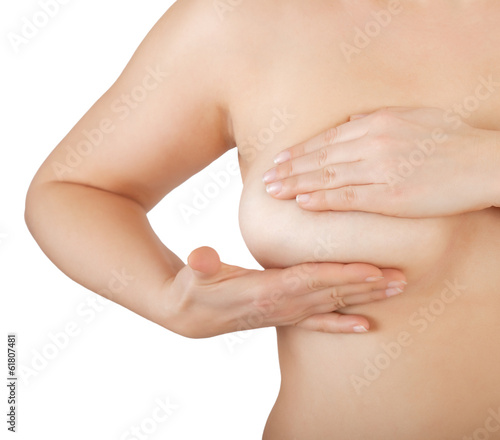 woman examining her breast for lumps