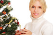 Beautiful woman near Christmas tree holding cup