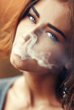 Portrait of a beautiful sexy girl with smoke from his mouth