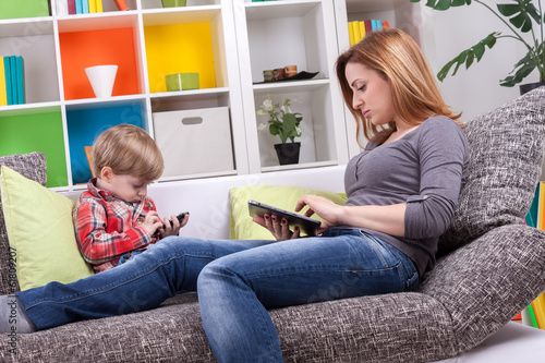 Mother and little boy playing with tablet and phone