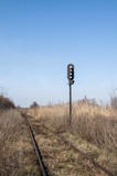 Abandoned rail line and empty railway traffic light in field