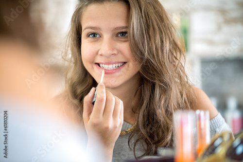 Cute girl applying  lip gloss