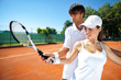 Woman and male tennis instructor practicing