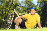 Mature man in sportswear sitting on grass near his bicycle