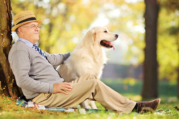 Senior gentleman and his dog sitting on ground in park