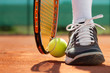 canvas print picture - Legs of athlete near the tennis racket and ball