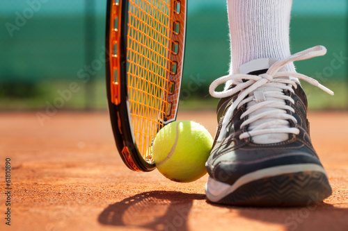 canvas print picture Legs of athlete near the tennis racket and ball