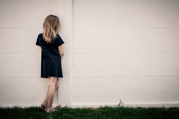 Portrait of sad little girl standing near wall in the day time