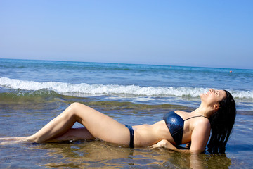 Beautiful female model laying in the sea with bikini laughing