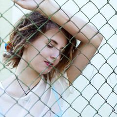 Close-up portrait of a girl with dreadlocks behind the grid