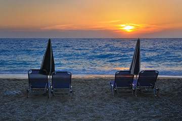 Isolated loungers and umbrellas on beach at sunset