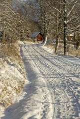 Gravel road with snow in a rural winter landscape.