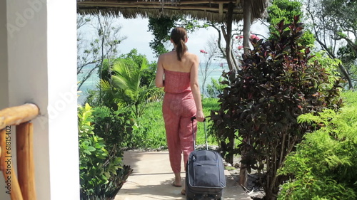 Woman with suitcase leaving hotel