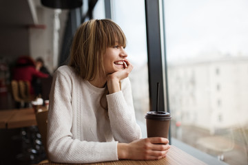 Beautiful cute girl in the cafe near the window with coffee