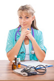 beautiful female doctor sitting at table and looking at camera