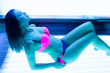 Beautiful young woman lying  in solarium
