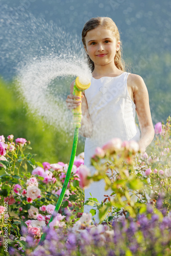 Summer garden, girl watering roses with gaden hose