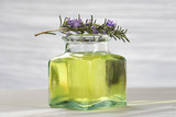bottle of aromatherapy oil and fresh green leaves