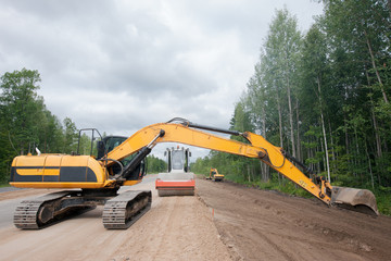 Excavator and roller compactor during road works