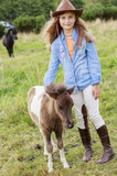 Little foal - cute girl takes care of the pony foal