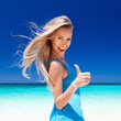 Happy blond girl on beach, showing okey sign.