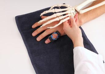 Handchirurg mit Skeletthand bei Patienten nach OP