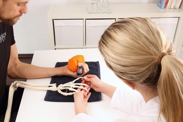 Handchirurg unterstuetzt Patient bei Bewergungsuebung