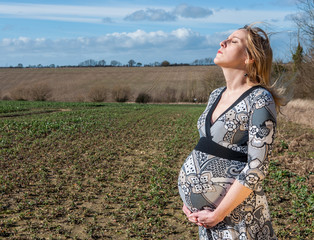 Pregnant woman standing in a field, week 38