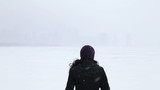 Woman looking out into lake and skyline during snow, video