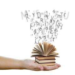 Mano con libros y letras saliendo de ellos sobre fondo blanco
