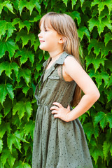 Summer portrait of a cute little girl against ivy