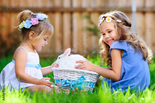 two little girl with a bunny rabbit has a easter at green grass