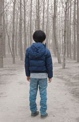 Asian boy standing in front of dry forest affected by pollution