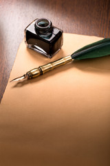 Quill pen and paper on wooden table