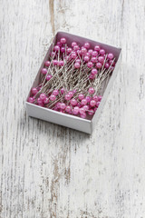 Box of sewing pins on wooden table