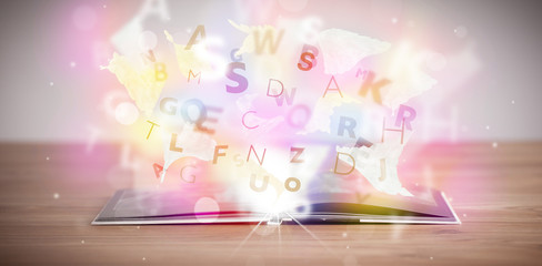 Open book with glowing letters on concrete background