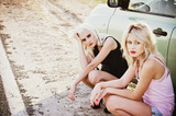 Two sad beautiful blonde girls sitting near broken car