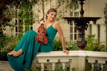 Beautiful brunette woman with a violin in her hands. plaza