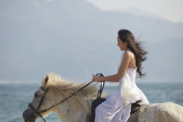 a woman riding horse on beach