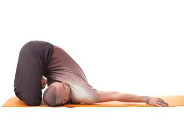 Flexible muscular man practicing yoga in studio