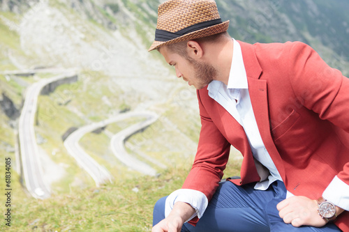 outdoor fashion man sits and looks down