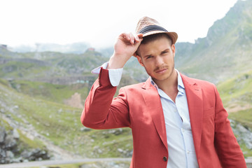 outdoor fashion man holds his hand on his hat